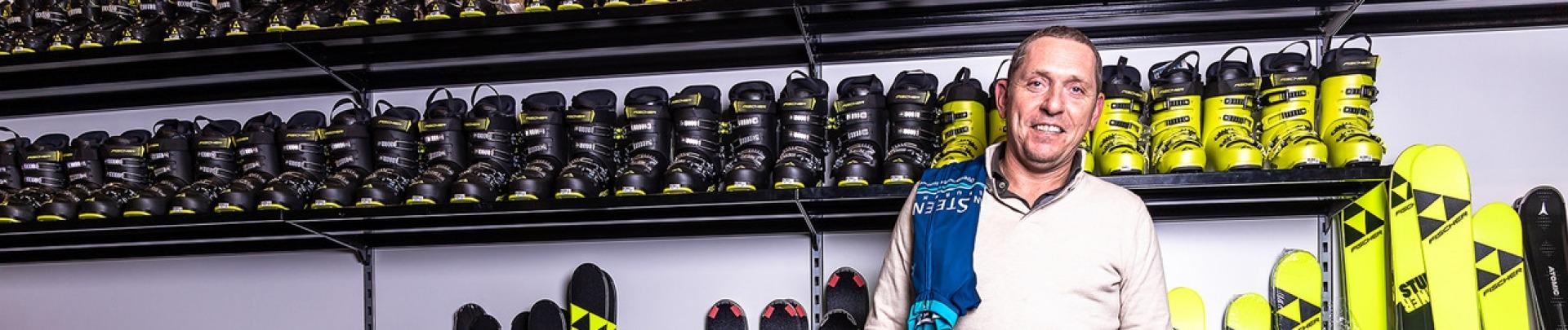 Een man voor een rek met skischoenen